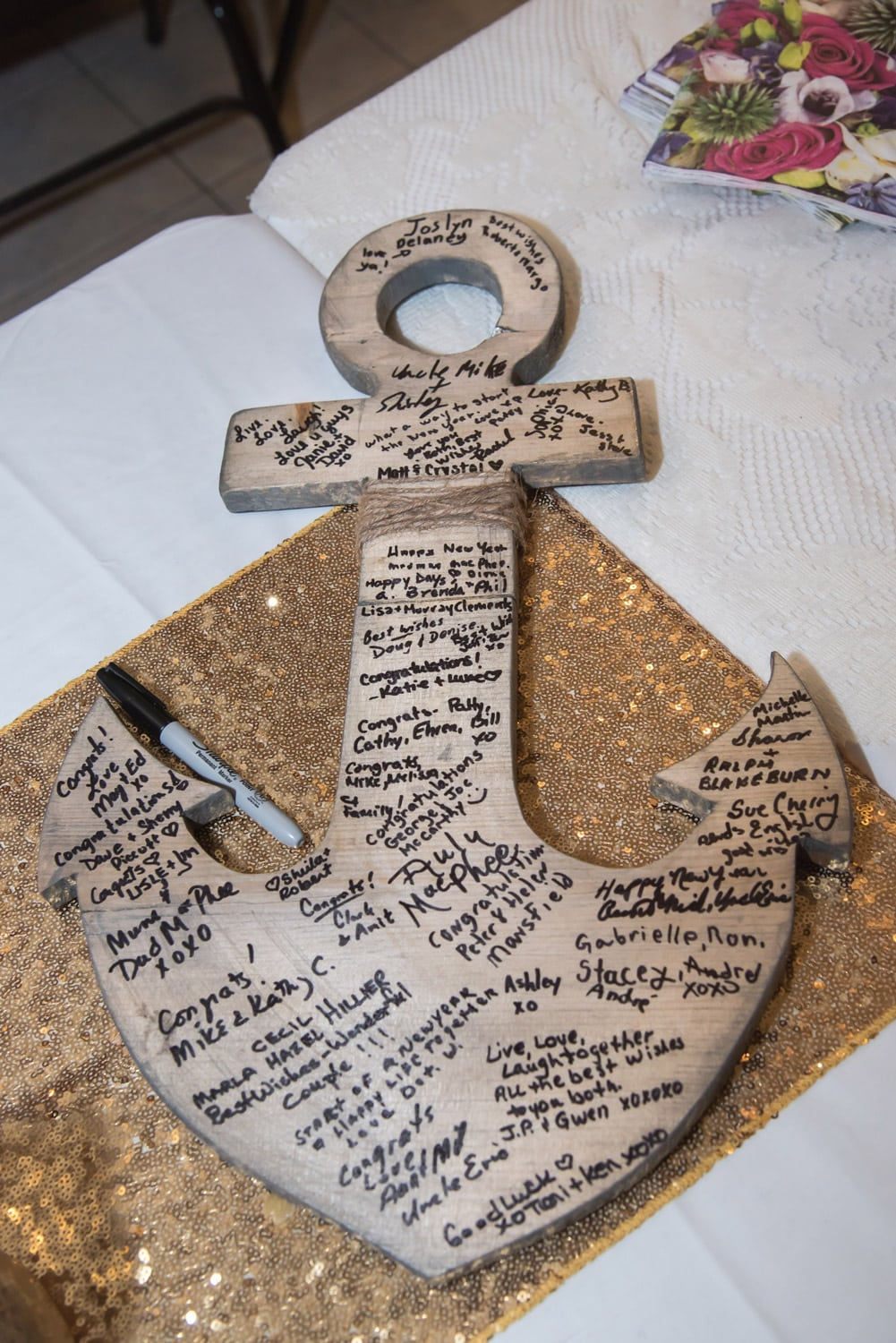 a wooden wedding guest book in the shape of a nautical anchor for wedding guests to sign
