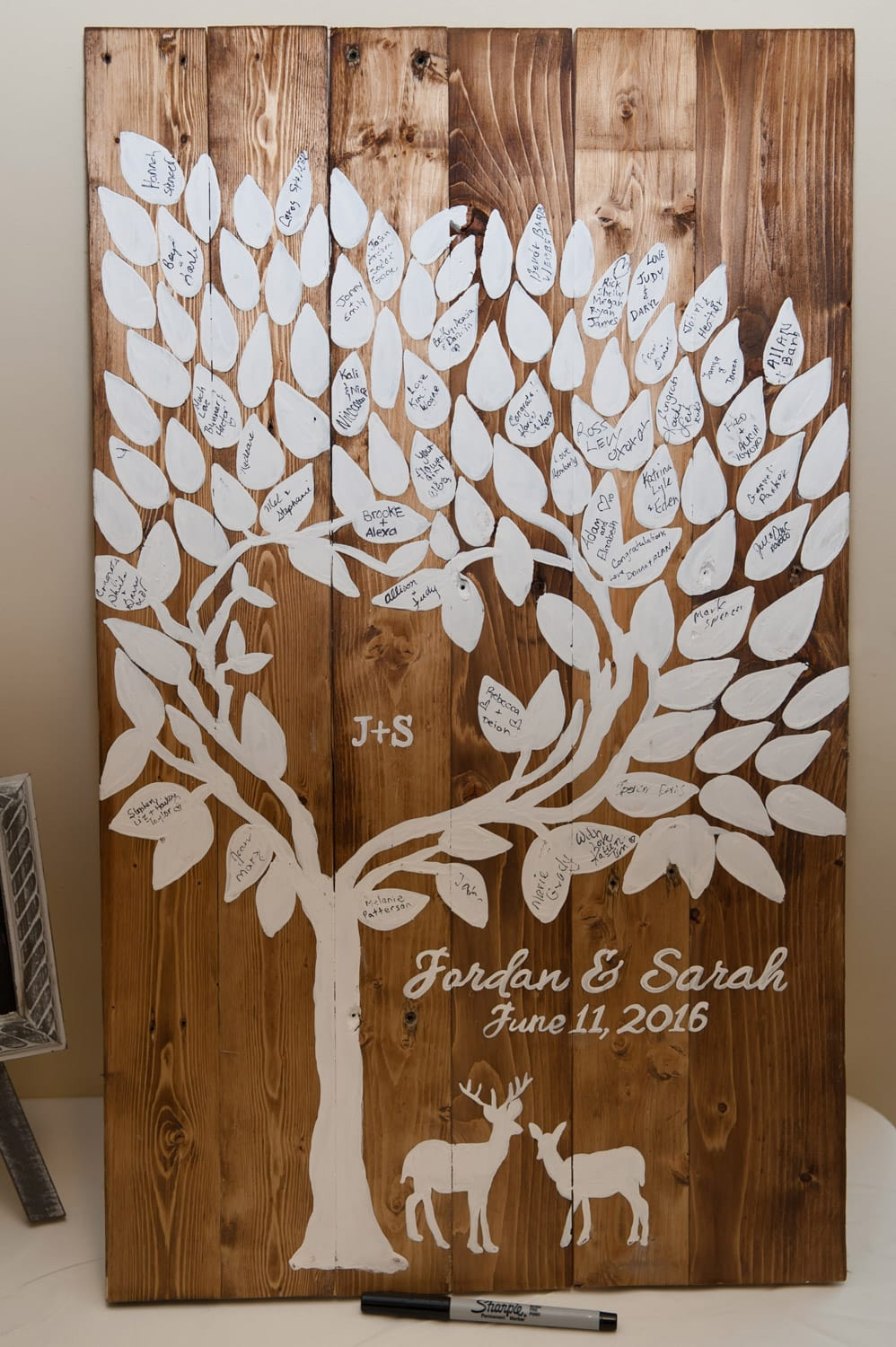 a wooden wedding guest book in the shape of a family tree for wedding guests to sign
